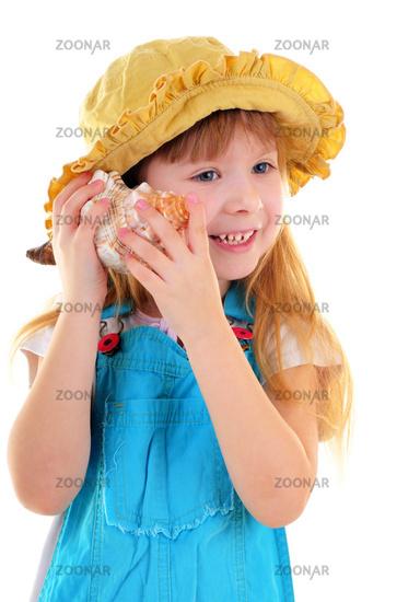 Nice smiling girl with sea shell