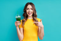 Pretty woman point to green detox vegetable smoothie