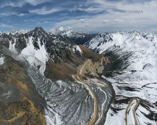 winding dirt road in the snow mountains