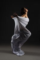 Seductive woman in white cloth standing gracefully in studio