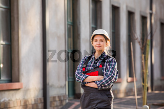Young girl, manual worker posing outdoors with hands folded on chest