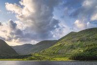 Gummeenduff lake and MacGillycuddys Reeks mountains illuminated by sunset light in Black Valley