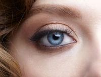 Closeup macro shot of blue human female eye. Woman with natural face beauty makeup.