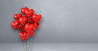Red heart shape balloons bunch on a grey wall background. Horizontal banner.