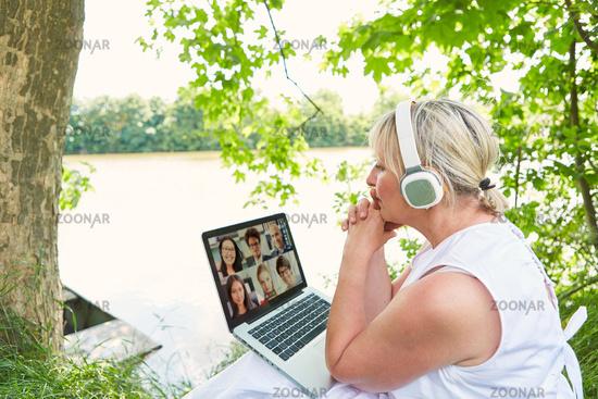Geschäftsfrau bei Videokonferenz am Computer in Natur