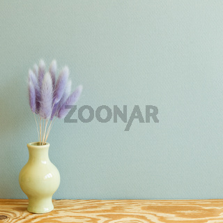 Vase of purple hares tail grass dry flowers on wooden table. mint wall background. copy space
