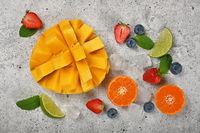 Fresh ripe mango and fruits on cutting board