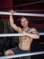 Muscular shirtless young man standing in gym