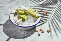 Frozen homemade pistachio popsicle in bowl of ice on gray background with palm leaf shadow in harsh light. Refreshing popsicle, frozen green juice on stick. Top view, copy space