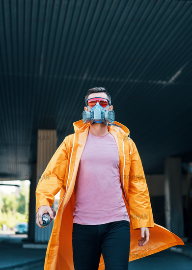 Trendy young man in respirator mask walking down the street