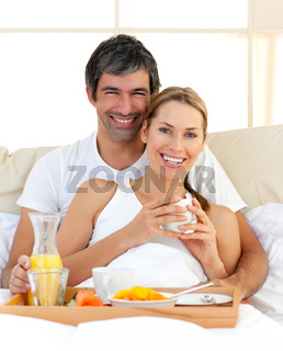 Smiling couple having breakfast lying in the bed