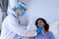 Caucasian female doctor in ppe suit checking african american female patient with ventilator