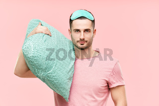 Young handsome man in sleeping mask holding pillow in hands