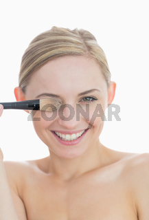 Closeup of playful woman covering eye with makeup brush