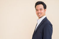 Profile view of Asian businessman wearing suit and smiling against plain background