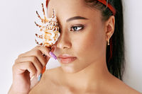 Pretty young afro woman covering her eye with sea shell
