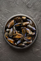 Fresh and raw sea mussels in black ceramic bowl placed on dark stone background