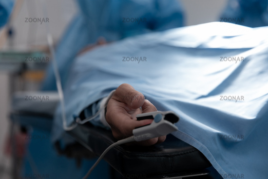 Patient lying on surgical bed wearing fingertip pulse oximeter in operating theatre