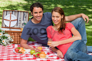 Two friends smiling while lying next to each other on a blanket with a picnic