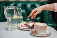 Closeup photo of female hands is reaching out to cake