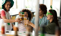 Diverse group of happy friends celebrating st patrick's day raising glasses of beer at a bar