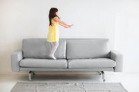 Little caucasian cute lovely girl in yellow dress playing and jumping on gray sofa in living room