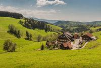 Traditioneller Schwarzwaldhof mit kleiner Kapelle in hügeliger Landschaft im Schwarzwald