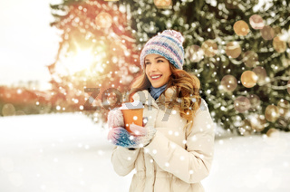 happy woman drinking coffee outdoors in winter