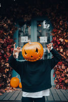 Girl with a pumpkin head scares at the camera
