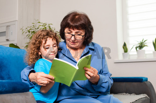 Grandmother and little girl reading book together