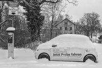 Winter in der Stadt - Elektroauto auf dem Parkplatz und zugeschneit.