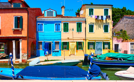 Cozy colorful houses and canal with boats in Burano