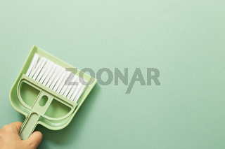Hand holding green broom and dustpan on green background. Cleaning housework concept. top view, copy space