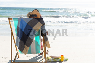 Mixed race woman on beach holiday sitting in deckchair relaxing