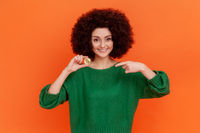 Portrait of pleasant looking woman with Afro hairstyle wearing green casual style sweater pointing finger at gold bitcoin, ecommerce.