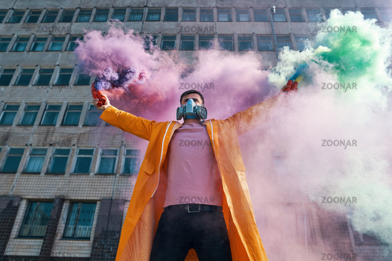 Young man in respirator mask hold smoke bombs in raised hands