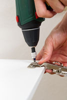 the carpenter screws the hinge on the furniture door. Furniture assembly service concept