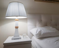 Luxury modern design of a bright bedroom with a bedside table and a night light and a pillow on the bed, preparing for bed, a glass of water