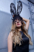 Young woman in black rabbit or hare masquerade fancy mask and black dress.