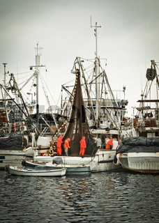 Fisherman crew fixing nets on fishing boat