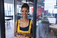 Portrait of mixed race female creative worker using smartphone and smiling