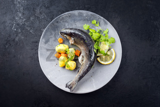 Modern style traditional steamed rainbow trout with boiled potatoes and carrot slices offered as top view on a design plate with copy space