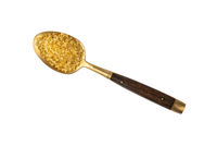 Vintage golden spoon full of brown cane sugar
