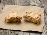 square baked cookie pieces lie on a piece of paper, wooden gray table, polish cookies