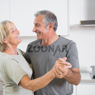 Smiling mature couple dancing together