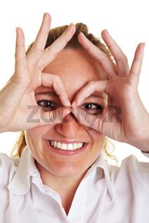 Frau bildet aus Fingern Kreise um die Augen