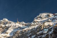 Der schneebedeckte Gipfel des Säntis mit Bergstation und fahrender Seilbahn, Schweiz