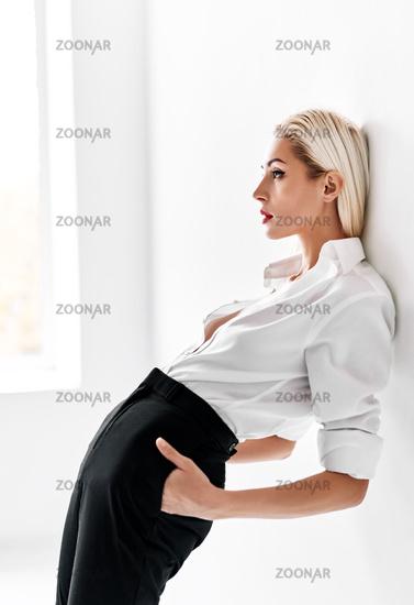 Sensual stylish blonde woman posing on white studio background