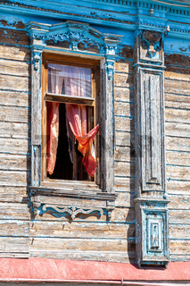Facade of an old house decorated with wooden carvings, platbands