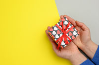 female hands hold cardboard box with red ribbon on yellow background, top view